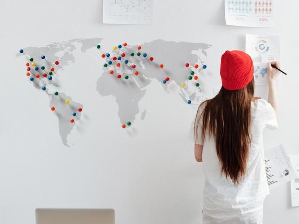 Donna scrive su una mappa del mondo