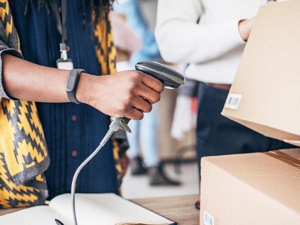 Donna scannerizza codice a barre di un pacco