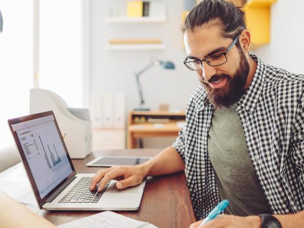 eBay-Verkäufer mit Bart arbeitet am Laptop
