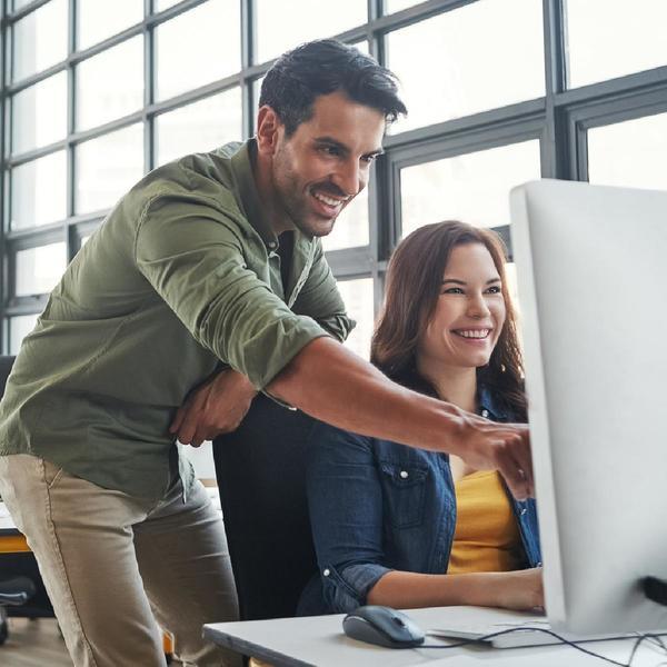 Uomo e donna sorridenti lavorano al computer
