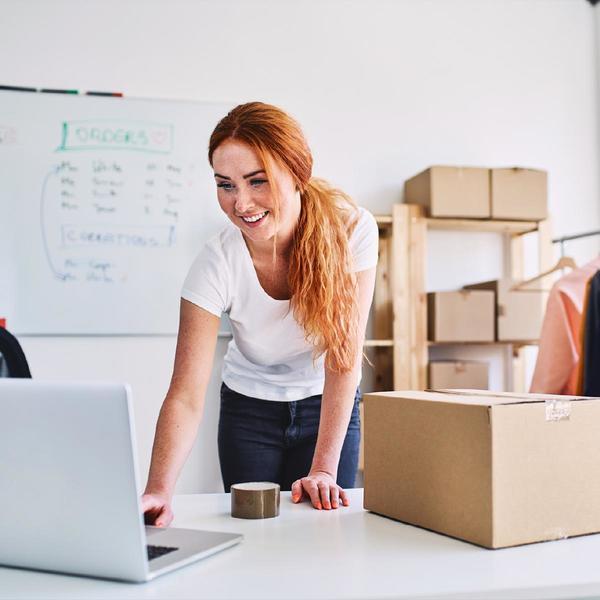 Donna sorridente lavora al computer, pacchi dietro