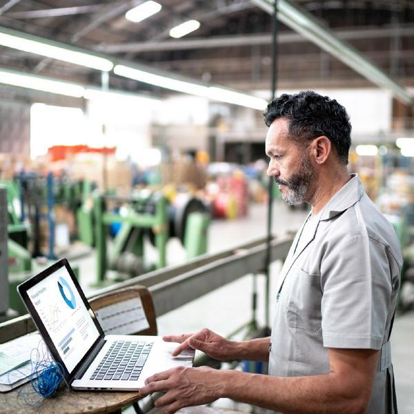 Uomo lavora concentrato al computer, merce dietro